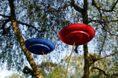 A red and a blue plate balanced on sticks beneath trees