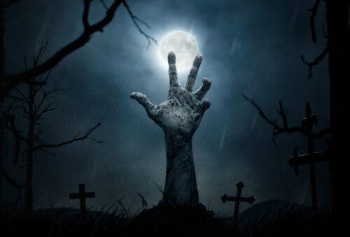 Zombie hand reaching out from grave with full moon in background