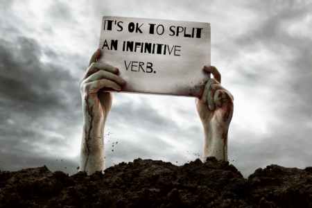 Zombie hands holding a sign that says It's OK to split an infinitive verb