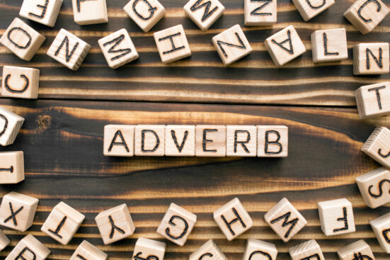 Adverb - word from wooden blocks with letters, describes or gives more information concept, random letters around, top view on wooden background