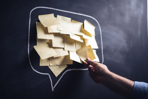 Speech balloon drawn on chalkboard filled with yellow sticky notes. A white hand places another sticky not in the balloon.