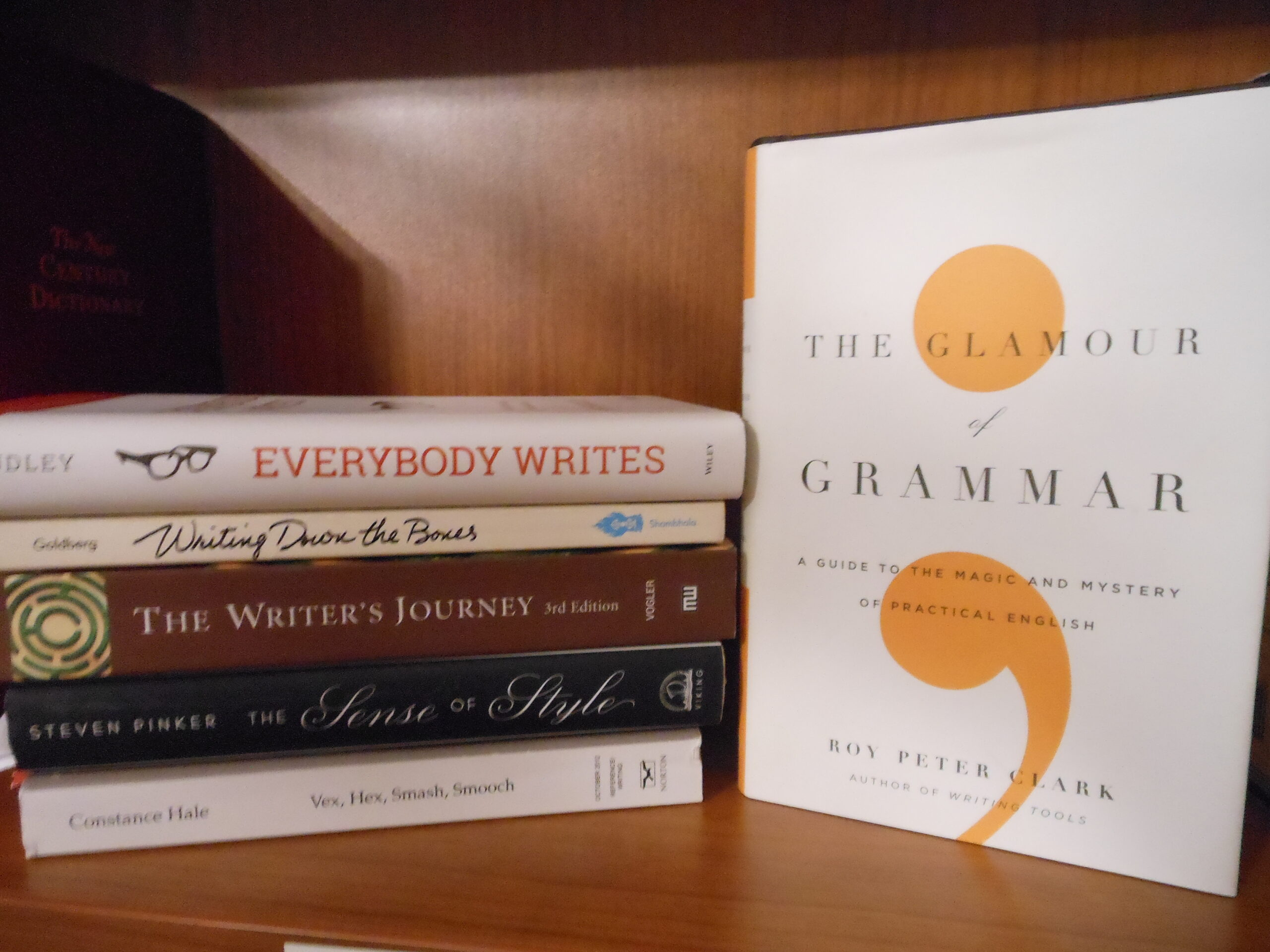 Books in a stack: Everybody Writes, Writing Down the Bownes, The Writer's Journey, The Sense of Style, Vex, Hex, Smash, Smooch. One book standing upright: The Glamour of Grammar