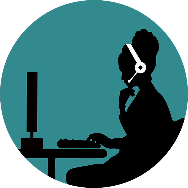 Silhouette of woman with headset on sitting in from of a computer