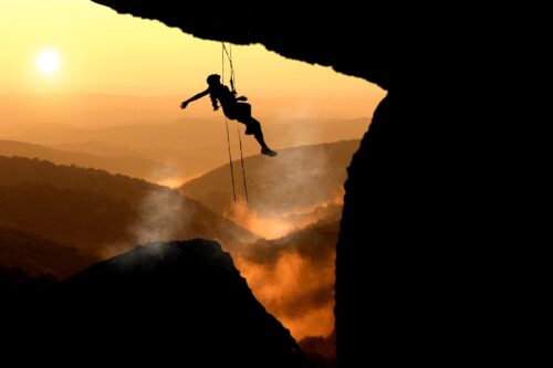 Woman in silhouette dangling from ropes while she mountain climbs